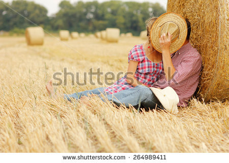 stock-photo-a-young-couple-in-love-on-haystacks-in-cowboy-hats-264989411
